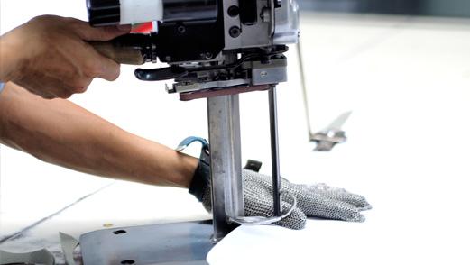 Die am Plotter ausgedruckten Schnittbilder werden auf die Stoffbahnen gelegt und mit Stoßmessern exakt zugeschnitten.
